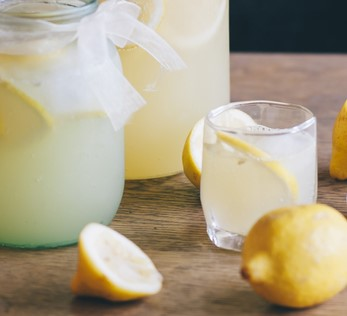 Fresh lemons and lemon drink in glass