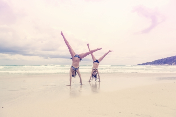 Quick and healthy energy boost - women on the beach cartwheeling
